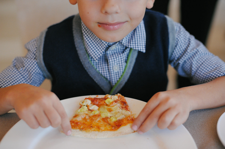happy little boy holding and eating pizza in cafe Stok Fotoğraf - 116438075