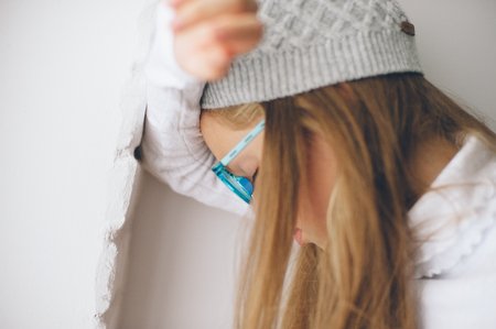 pensive little girl in wool cap leaning on wall with closed eyes in glasses Stok Fotoğraf - 116438072