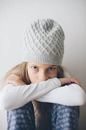 small caucasian little girl in woolen hat sitting indoors pensive