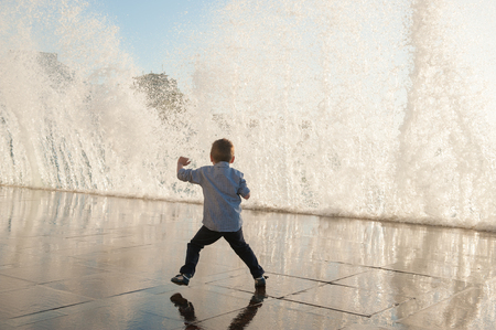 one little kid escaping frome huge wave on sea shore in city during storm weather Stok Fotoğraf