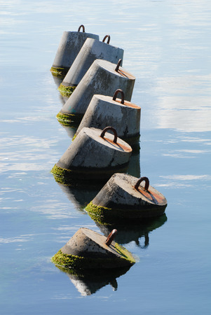 vertical composition of several concrete breakwater in sea water Stok Fotoğraf - 116435654