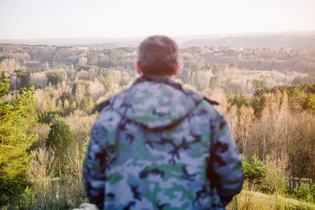 man in jacket watching at beautiful spring mountain landscape during recreation hiking