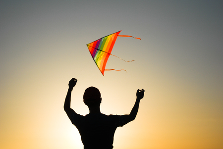 silhouette of young man with flying colorful kite on sunset sky background