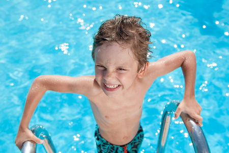 adorable little wet kid near outdoor swimming blue pool during holiday