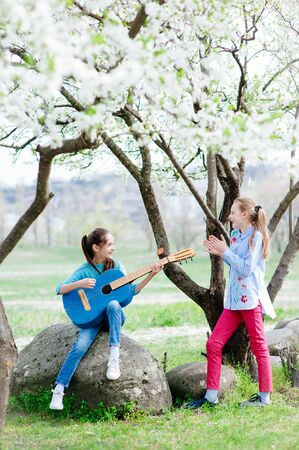 happy little girls outdoors rehearsal with guitar and singing in blossom spring park