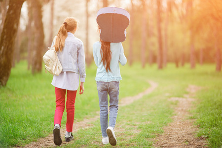 lifestyle concept two children girls with guitar and backpack walking along path in spring forest Stok Fotoğraf