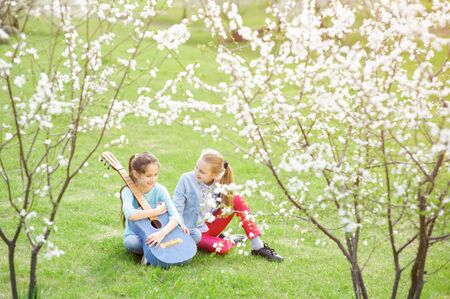 two happy smiling little girls with acoustic guitar sitting on green grass under flowering trees in springtime