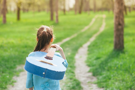 concept of young musician small girl walking outdoor spring park along trail carrying acoustic Spanish denim guitar on her shoulder Stok Fotoğraf