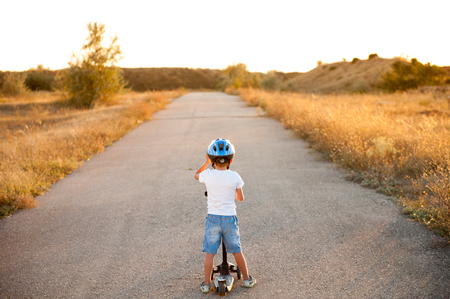 active healthy little boy in helmet standing on empty road with scooter in sunset Stok Fotoğraf