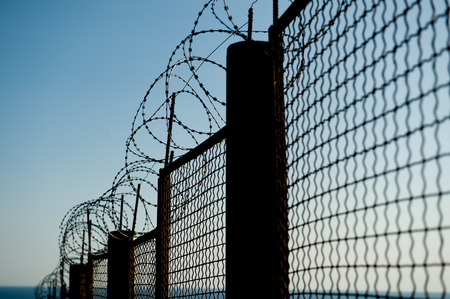 razor barbed wire on high steel fence on blue sky Stok Fotoğraf - 122665163