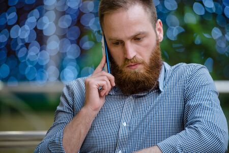 handsome bearded young caucasian man calling holding cell phone standing indoors with background with blue bokeh Фото со стока