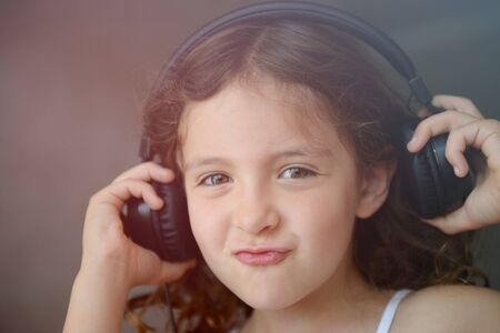 pretty little girl in headphones listen music sound with pleasure grimace on her beautiful young face