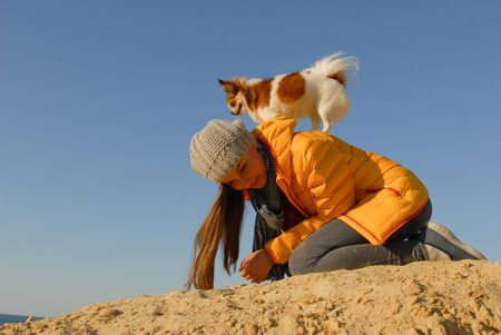 young active woman in wool hat and autumn yellow jacket with little chihuahua dog on her back during outdoor animal trick training Stok Fotoğraf