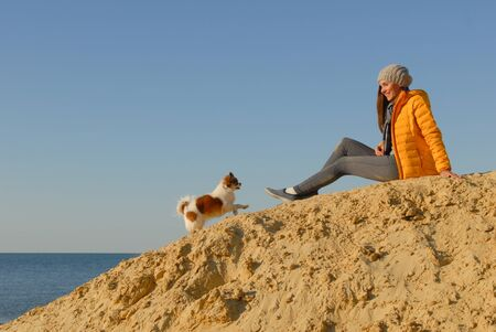 active little chihuahua dog running up on sand hill to her happy woman owner in autumn clothes on blue sky and sea background