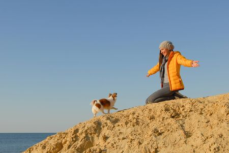 happy hospitable girl owner meet her little chihuahua pet canine dog walking on sand hill with open arms