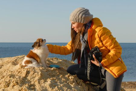 young beautiful woman in woolen hat and yellow jacket prepare little chihuahua dog for photo shoot