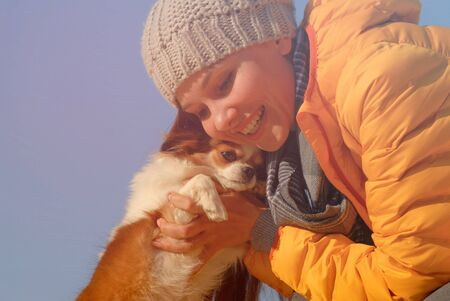 happy beautiful canine owner young woman in autumn wool cap scarf and yellow jacket hugging her small chihuahua pet dog with smiling on her face