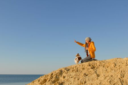 animal training concept young woman in yellow jacket sitting on sand hill on sea beach making orders for little dog chihuahua