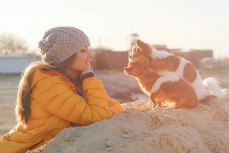 pretty young happy smiling woman in wool cap and yellow jacket looking at her funny chihuahua little pet dogs hugging each other on sand beach Stok Fotoğraf