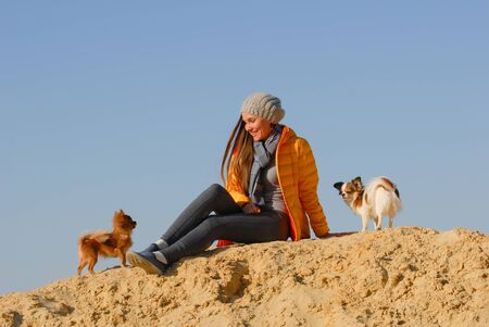 active happy pretty young woman in autumn clothes sitting on sand hill during outdoor leisure vacation