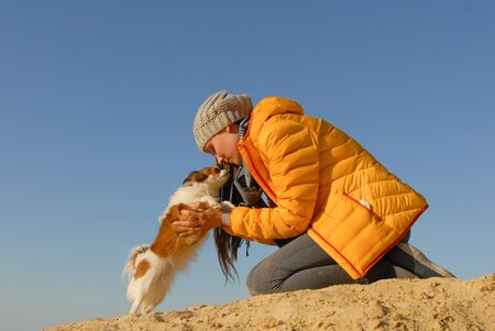 close relationship of young woman and her little dog hugging on sand beach in spring Stok Fotoğraf