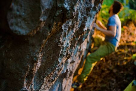 young active sport man climbing on outdoor rock during bouldering training on warm sunset Stok Fotoğraf