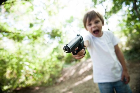 aggressive shouting child threatens with real gun in USA outdoor park Banque d'images