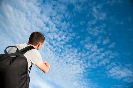 active healthy young man with backpack control flying kite in blue cloud sunset summer sky
