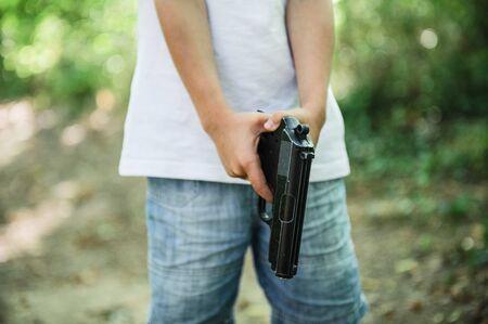little boy in white shirt holding black gun get ready to shoot Stok Fotoğraf