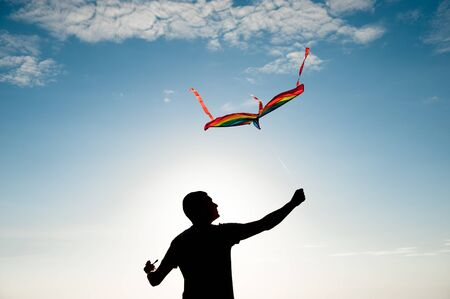 freedom concept of adult active man holding flying multicolored kite in blue sky in summer