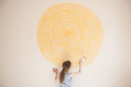 talent art little artist girl painting yellow sun circle on beige wall using paint brush