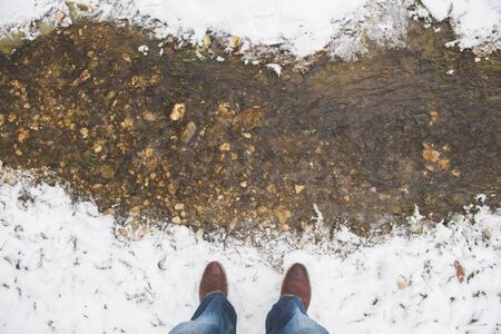 human feet male wearing winter boots and jeans standing on bank of little spring creek covered with white fresh clean snow