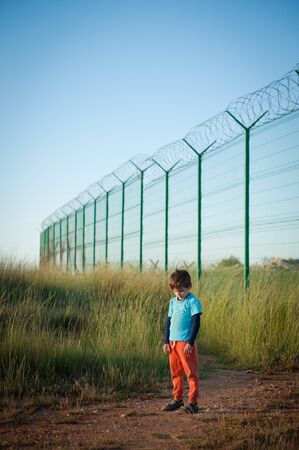 one lonely poor kid refugee standing sad on state border with high fence with barbed wire