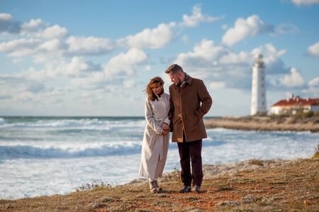 relationship concept young man and woman in autumn coat walking along stormy sea coast with lighthouse Stockfoto - 131032331