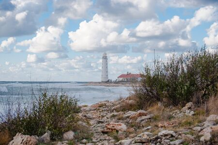 outdoor landscape with sea stormy shore and white beacon on horizon with beautiful clouds Stok Fotoğraf