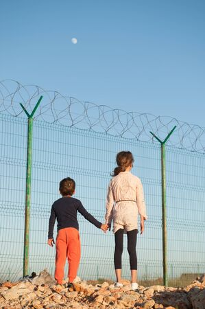 poor refugees kids on state border with high fence with barbed razor wire and moon in sky holding hands with hope for care