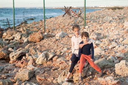 illegal immigration concept of two poor little children family brother boy and girl sister hugging sitting on stone on sunset coast with state border fence