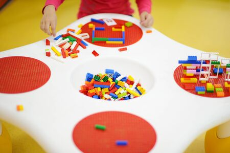 active little child in pink shirt playing colorful construction toy during leisure activity