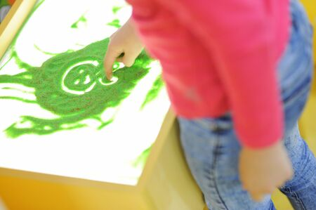little child in pink shirt and jeans drawing picture with finger using green toy sand on bright surface Stok Fotoğraf