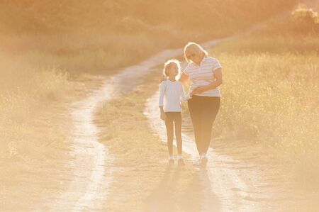 happy family grandmother fat woman hugging little thin little girl during outdoor leisure sport activity backlit with sunset with copyspace 写真素材