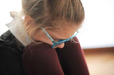 triste petite fille consciente en uniforme scolaire et lunettes se penche la tête sur les genoux pendant une situation de stress