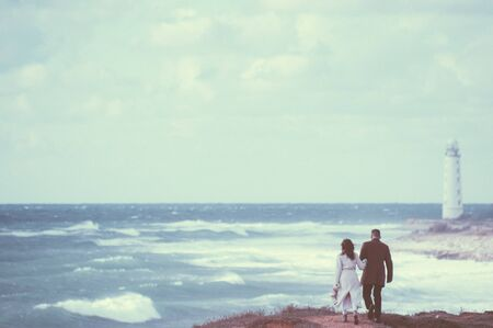 vintage picture of young couple in autumn coat walking along stormy sea shore with high waves and lonely lighthouse on edge of world Stockfoto