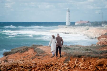 young pair man and woman in coat walking along stormy sea coast with beacon
