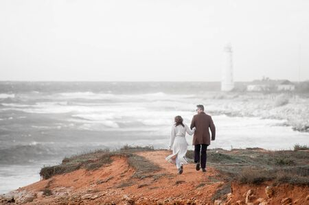 young couple in coats man and woman walking along sea beach with lighthouse in mist during autumn travel Stockfoto