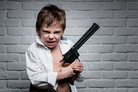 angry little boy in white shirt holding long revolver gun on brick wall backdrop 写真素材