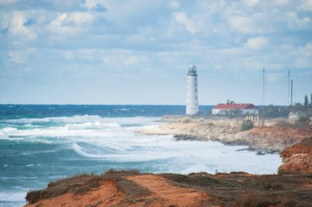 beautiful seascape with sea shore on foreground and white lighthouse on background during storm weather with waves