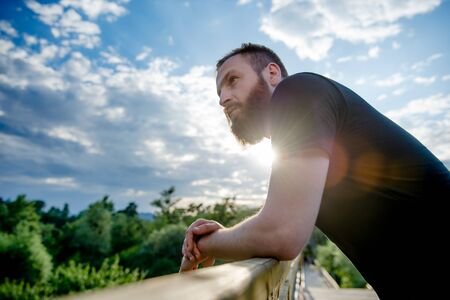 cute healthy man with beard leaning on wooden bridge resting after workout in summer park with blue cloudy sky and sun beam