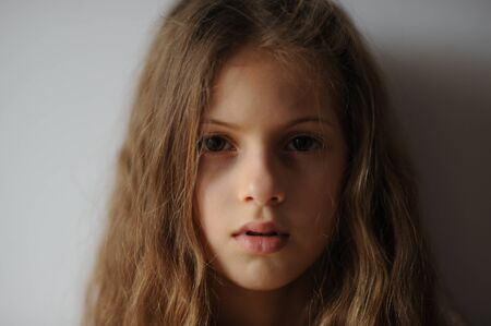 portrait of pensive beautiful little girl with long hair and serious face