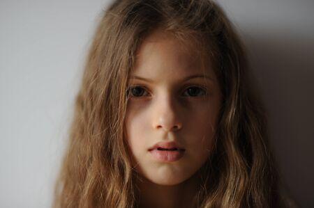 Retrato de una hermosa niña pensativa con cabello largo y rostro serio