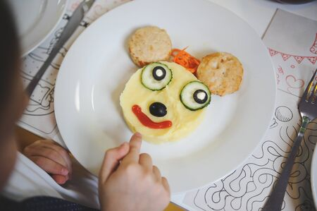 little boy pointing his finger at plate with funny tasty dish with cartoon character face from food Imagens